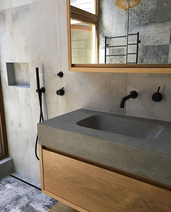 a minimalist concrete bathroom with a concrete countertop and a sink plus items of light stained furniture