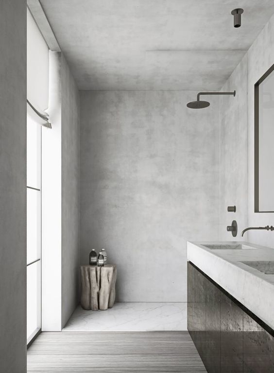 a minimalist concrete bathroom with a frosted glass wall, a floating vanity with a concrete countertop and dark fixtures