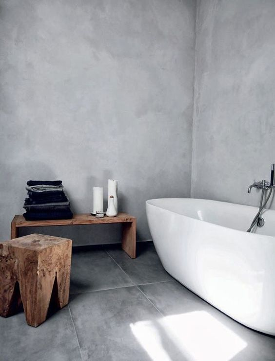 a minimalist concrete bathroom with rough wooden furniture and a stylish bathtub, it's welcoming and airy