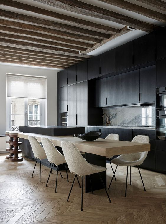 a minimalist kitchen with black cabinets, a marble backsplash, a two-part kitchen island and rough wooden beams