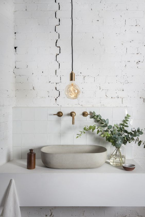 a minimalist white bathroom with a brick wall, a floating vanity with a concrete sink, a bulb and brass fixtures