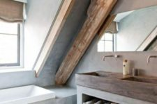 a modern bathroom done with concrete, with wooden beams, a concrete vanity and a wooden sink plus a window