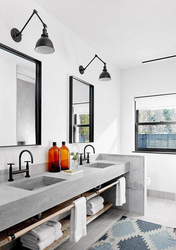 a modern bathroom with a built-in concrete vanity and a half wall, catchy black sconces, black fixtures and mirrors in black frames