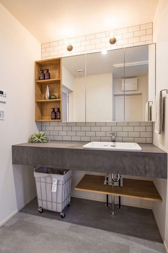 a modern bathroom with white subway tiles, a concrete vanity with a sink, mirror and wooden storage cabinets