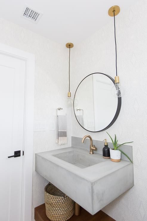 a modern bathroom with white tiles on the walls, a floating concrete sink, a round mirror, bulbs hanging down and a basket for storage