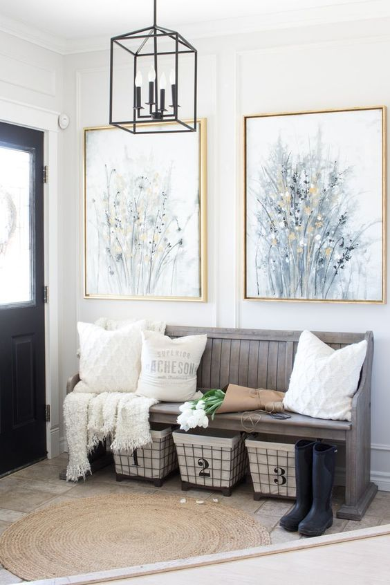 a modern farmhouse entryway with a weathered wood bench, wire baskets for storage, neutral pillows and artworks