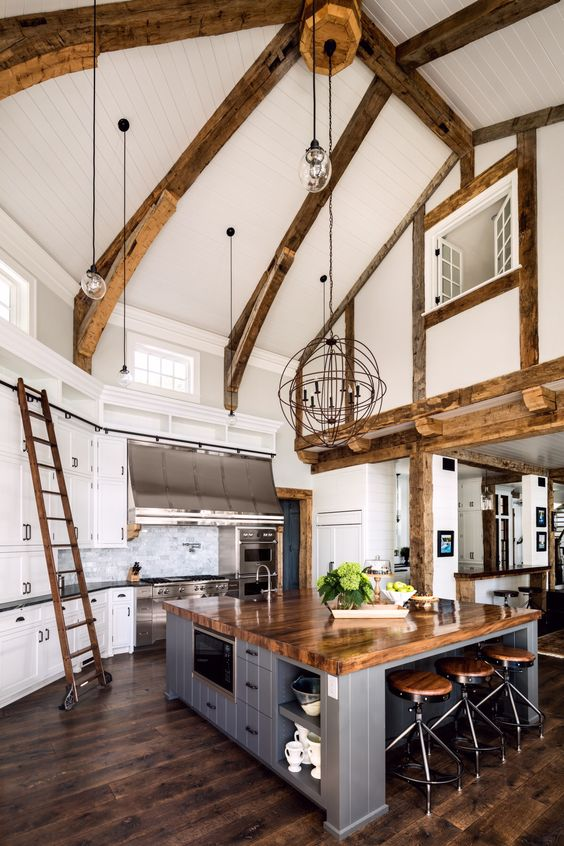 a modern farmhouse kitchen with white cabinetry, a grey kitchen island, wooden beams and countertops and pendant lamps