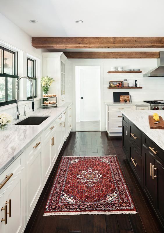 a modern farmhouse kitchen with white cabinets, a black kitchen island, wooden beams, a bright rug and gold touches is wow