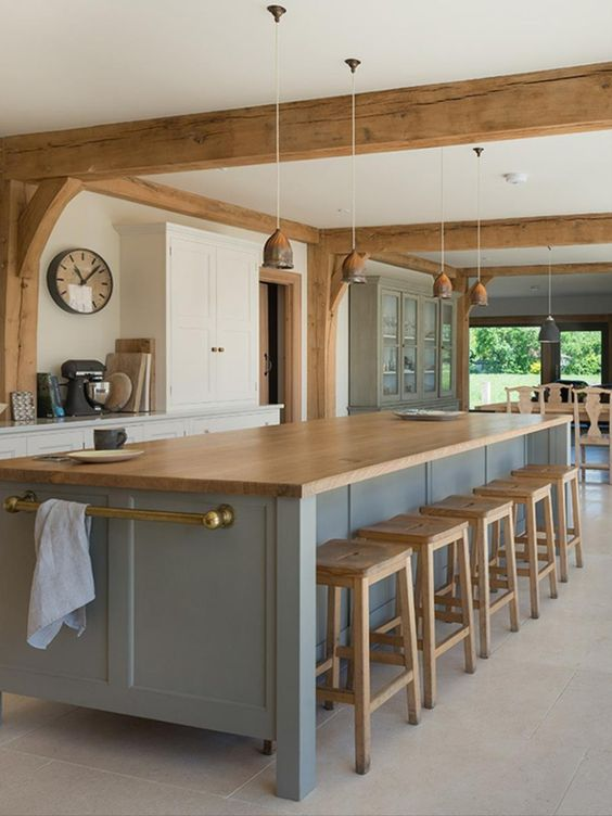 a modern farmhouse kitchen with white cabinets and a blue kitchen island, wooden beams and stools, pendant lamps for eye-catchiness
