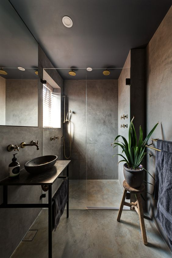 a moody concrete bathroom with a wall-mounted vanity and a round sink, a wooden stool and a window in the shower plus vintage fixtures