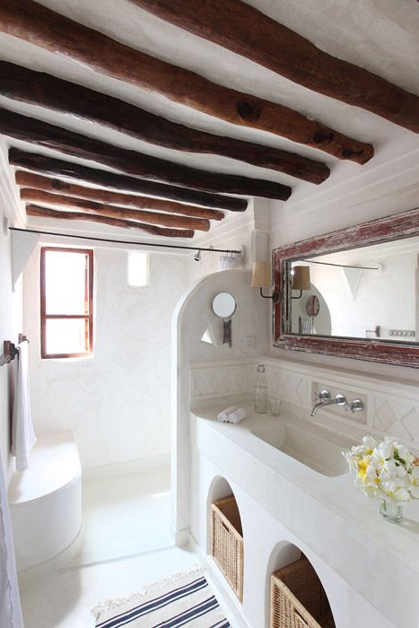 a neutral bathroom in white, with rich stained beams, a shower space and a concrete vanity with storage space