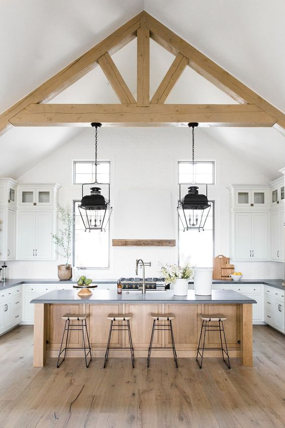a neutral contemporary kitchen with dark stone countertops, wooden beams, a wooden kitchen islnd is welcoming and stylish