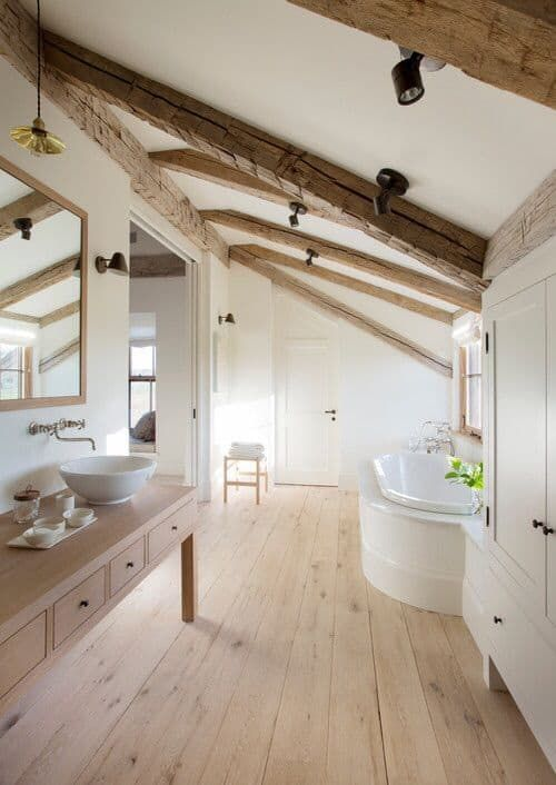 a neutral farmhouse bathroom with a large vanity, wooden beams on the ceiling, a large storage unit and a built-in tub