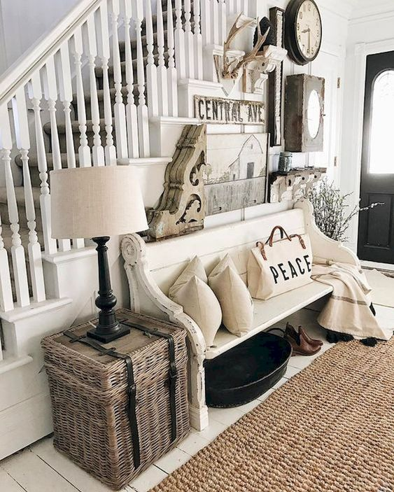 a neutral farmhouse entryway with a large and creative gallery wall, a white bench, neutral pillows and blankets plus a woven box