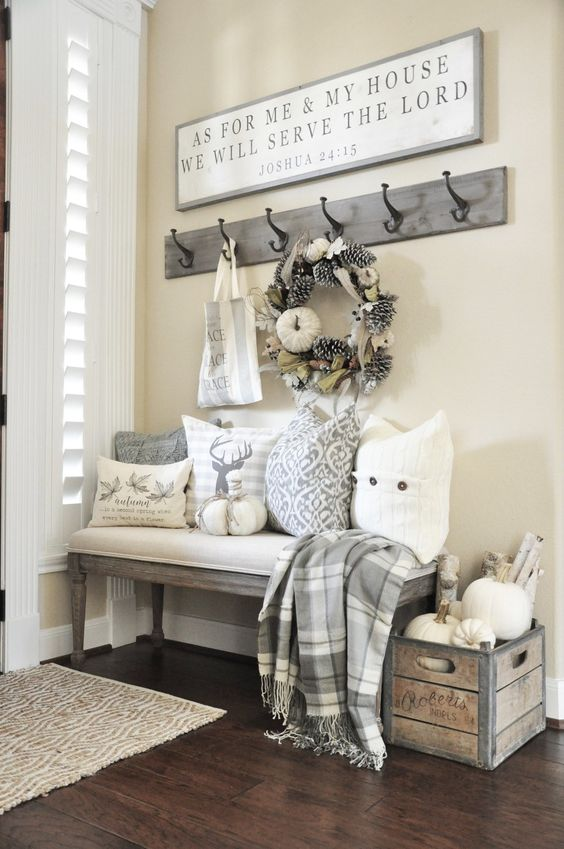 a neutral farmhouse entryway with an upholstered bench, printed pillows, a crate with branches and pumpkins, a rack with hooks and a sign