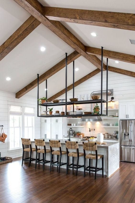 a neutral farmhouse kitchen clad with beadboard, with white cabinetry, woven stools, wooden beams and a pendant storage unit