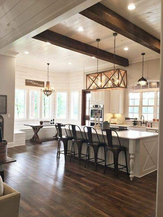 a neutral farmhouse kitchen with grey cabinetry, dark chairs and a table, pendant lamps and a wooden chandelier