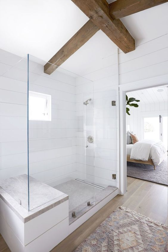 a neutral modern farmhouse bathroom clad with white wood, with dark stained beams and neutral tiles