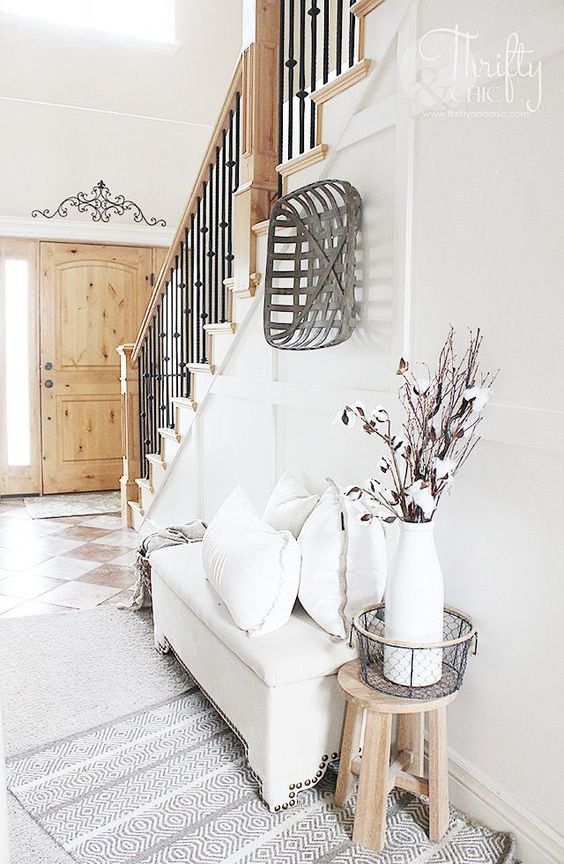 a neutral modern farmhouse entryway with a white upholstered bench, a wooden basket and some cotton branches in a vase