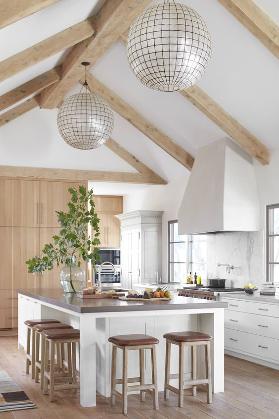 a neutral modern farmhouse kitchen with white cabinets and a kitchen island, a marble backsplash, light-colored wooden beams and sphere lamps