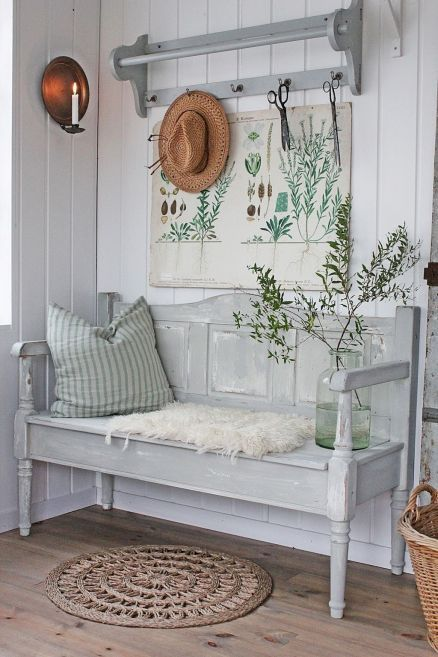 a neutral vintage farmhouse entryway with a grey bench, a vintage poster as an artwork, a rack and a pillow