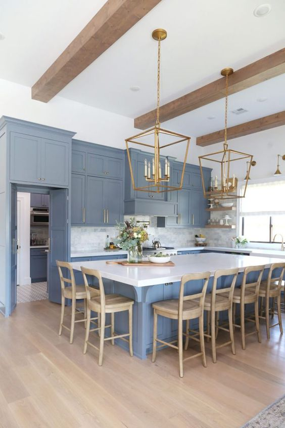 a refined blue kitchen with white surfaces, wooden beams, wooden chairs and brass chandeliers is stylish and chic