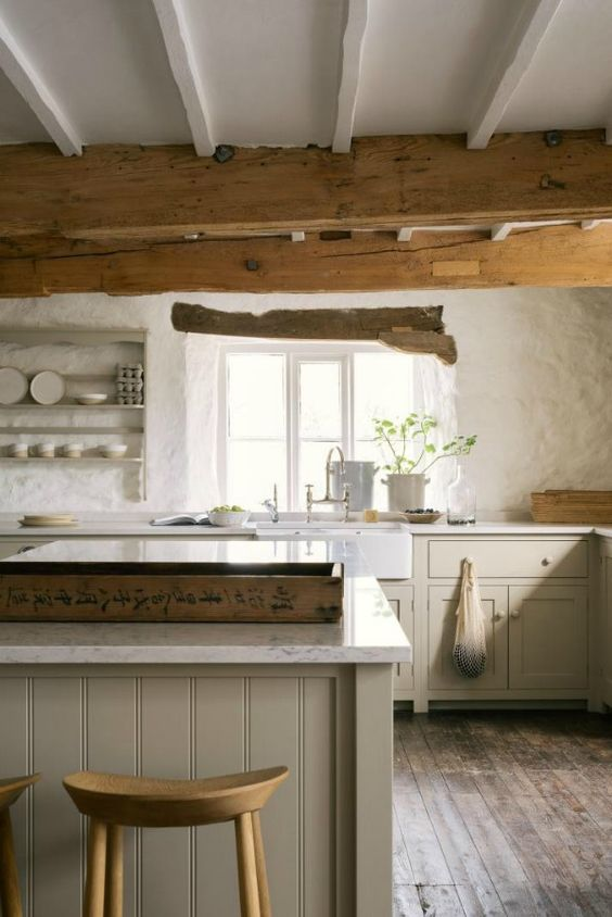 a rustic English country kitchen in light grey, white textural walls, wooden beams on the ceiling for a cozy feel