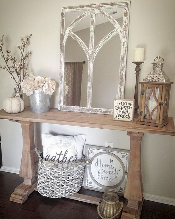 a rustic console table with a metal bucket, a mirror in a vintage frame, a pumpkin and a woven basket with a pillow