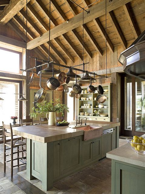 a rustic kitchen with green cabinetry, wooden and stone countertops, a wooden ceiling with beams is a chic space
