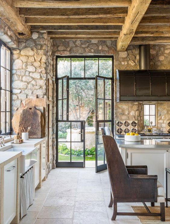 a rustic kitchen with stone walls, wooden beams and ceiling for much coziness and white cabinetry plus leather chairs