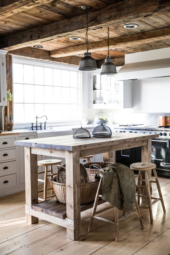 a rustic kitchen with white cabinetry, a rough wooden kitchen island, wooden stools, a wooden ceiling and beams, pendant lamps is very cozy