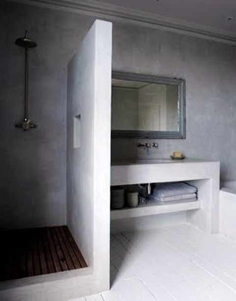 a sleek minimalist concrete bathroom with a built-in vanity, a shower space with a wooden floor and a tub clad with concrete