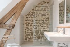 a small neutral bathroom with wooden beams, a stone wall, a wall-mounted sink and a wooden chair plus a window