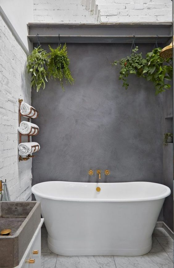 a stylish bathroom with white brick walls and a white stone floor, an oval tub and a concrete wall and sink