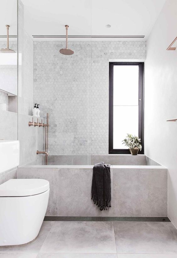 a stylish contemporary bathroom with a concrete wlal and bathtub, a marble penny tile wall and metallic fixtures