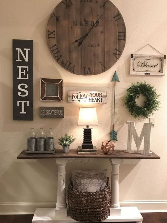 a vintage farmhouse console with a basket for storage, a gallery wall with signs and a large clock