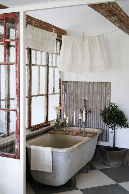 a vintage industrial bathroom with a concrete tub, shabby chic windows, some potted plants and candles