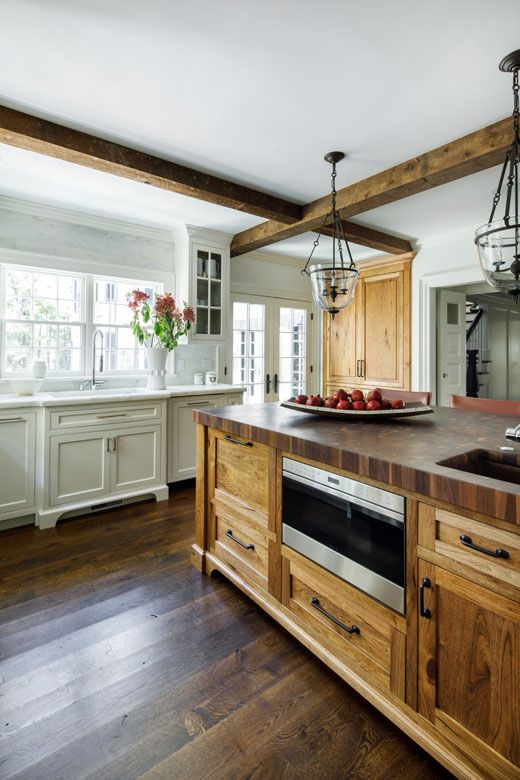 a vintage kitchen with neutral cabinets, a stained wooden kitchen island and wooden beams that match and look cozy