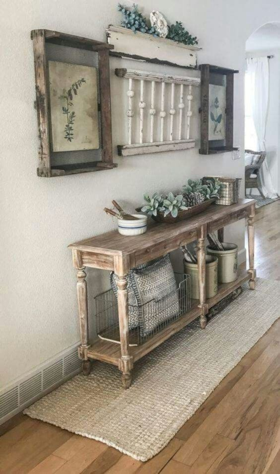 a vintage meets farmhouse entryway with a wooden console, vintage posters as artworks and some jute integrated