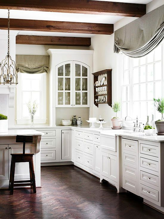 a vintage white kitchen with elegant cabinetry, dark wooden beams and sotols that add interest, grey and green curtains