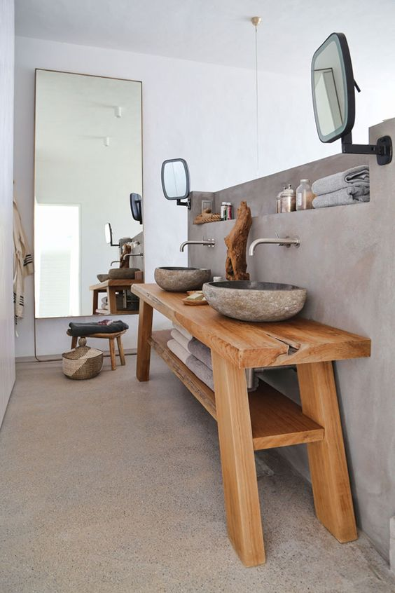 a wabi-sabi bathroom with a concrete floor and wall with a built-in shelf, a wooden vanity with stone carved sinks and a mirror