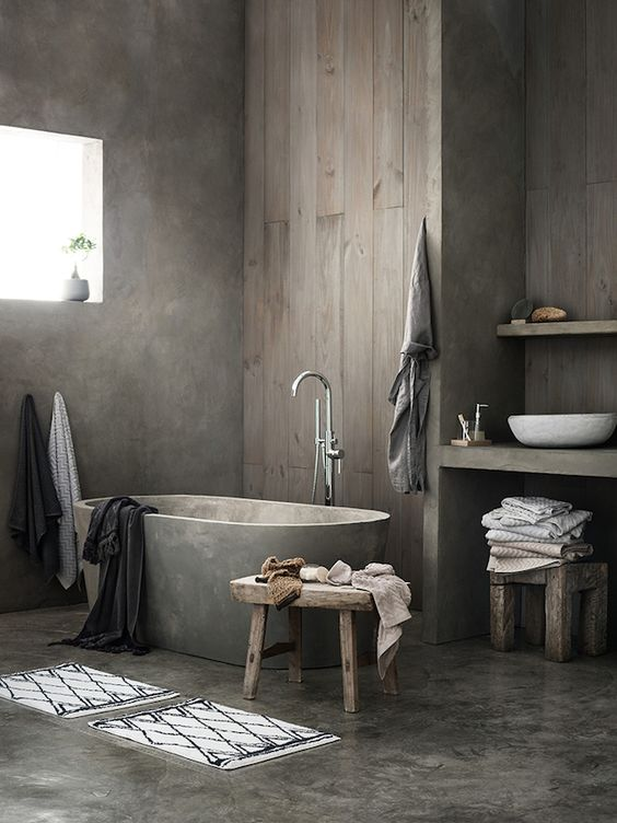 a wabi-sabi to Nordic bathroom with a concrete floor and walls, a concrete tub, a wooden wall and a built-in vanity plus a round sink