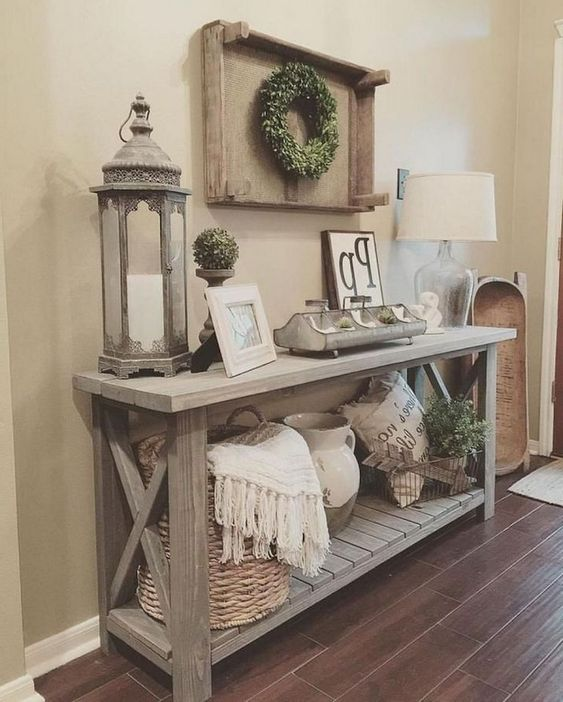 a weathered wood rustic console table with a basket with blankets, a candle lantern, some boxwood and a dough bowl
