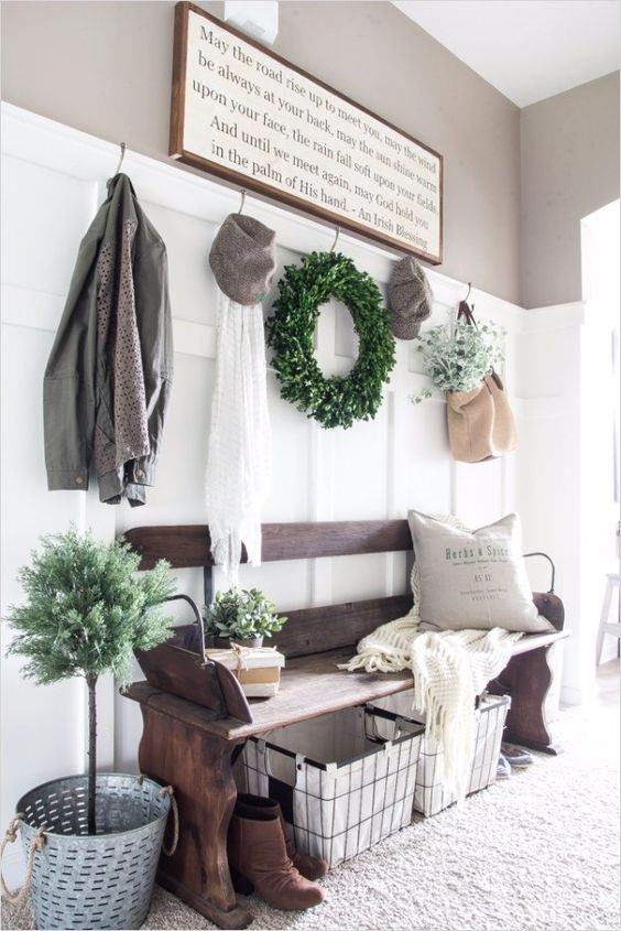 a welcoming farmhouse entryway with a weathered wooden bench, a wire basket, a sign, some decor and a boxwood wreath