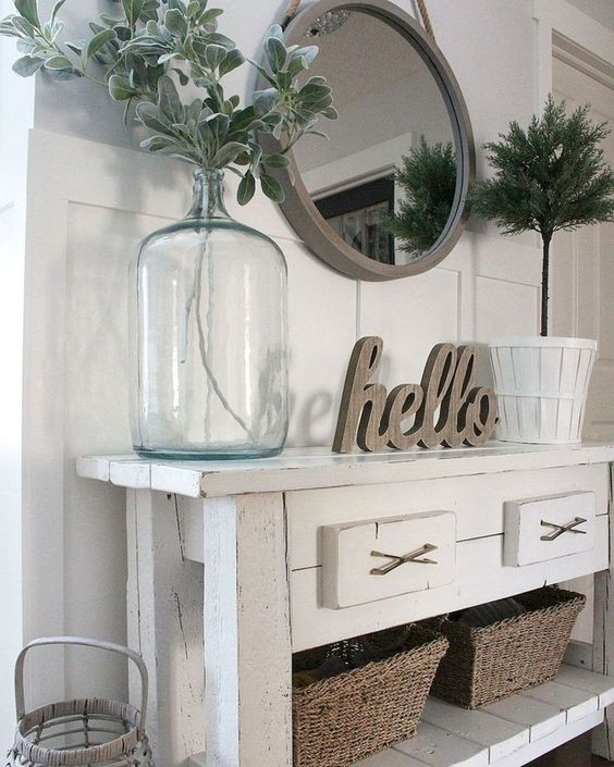 a white console table, baskets for storage, a round mirror in a wooden frame and some greenery in a bottle