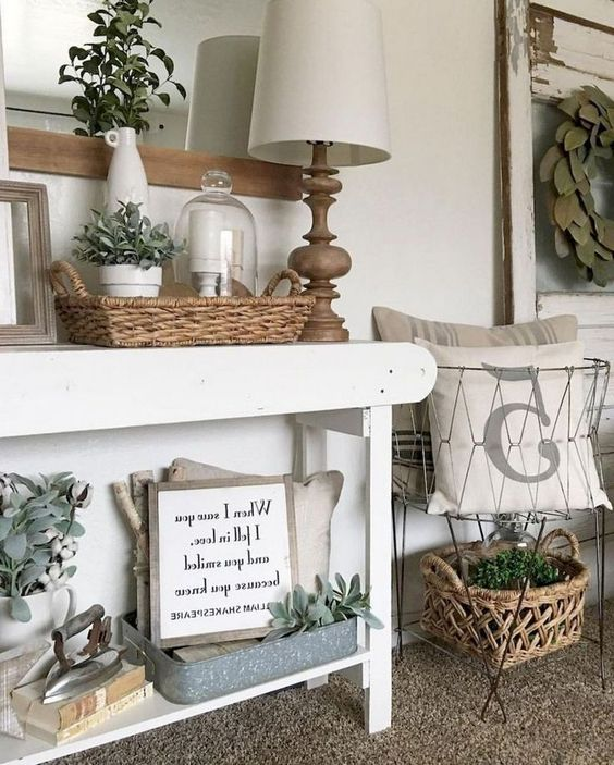 a white farmhouse console with baskets, wire baskets, a table lamp and much greenery for a vintage feel