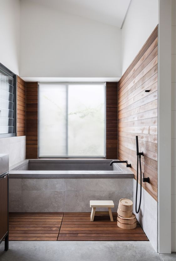 a zen Japanese bathroom with a bathtub clad with concrete and tiles, stained wood on the floor and walls is welcoming