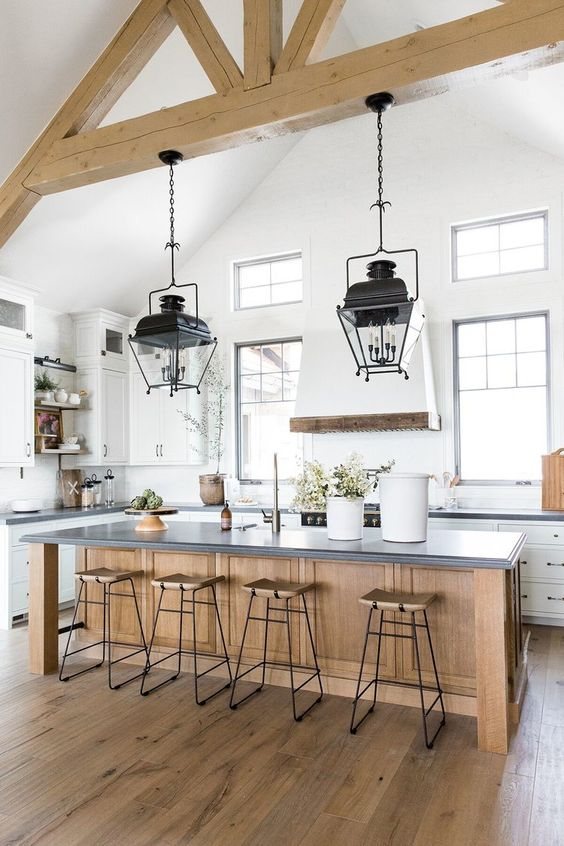 an airy and chic white kitchen with a wooden kitchen island and wooden beams on the ceiling plus refined vintage lamps on them