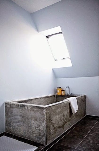 an attic bathroom with a concrete bathtub and black tiles on the floor is a gorgeous contemporary space that feels airy
