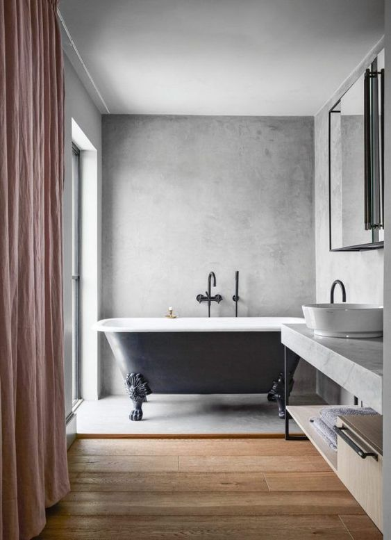 an eclectic bathroom with concrete walls and a floor, a wooden floor and a concrete vanity, a large mirror and a window